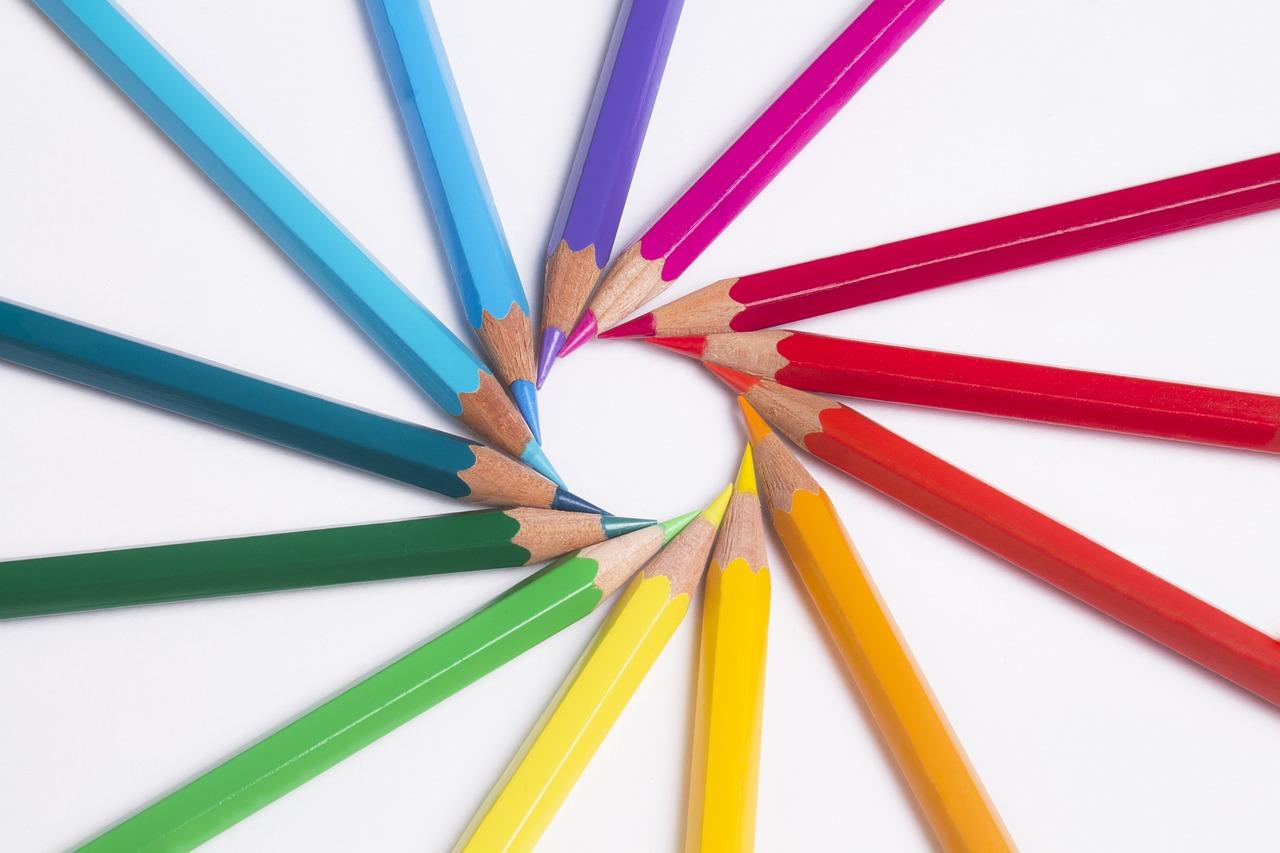 Buntstifte in den Farben des Regenbogens zu einem Kreis angeordnet
