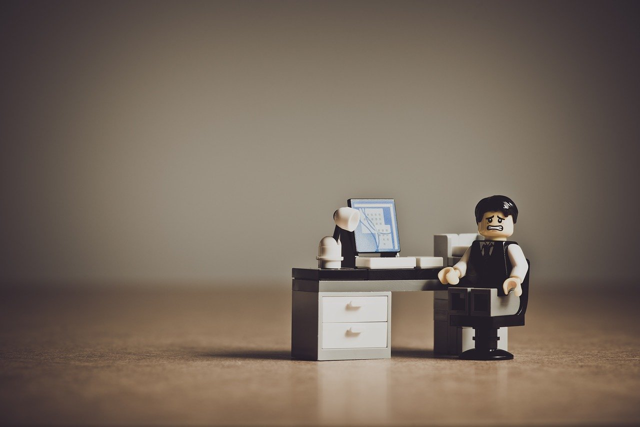 Ein Legomännchen mit verzweifeltem gesichtsausdruck an einem Schreibtisch aus Lego