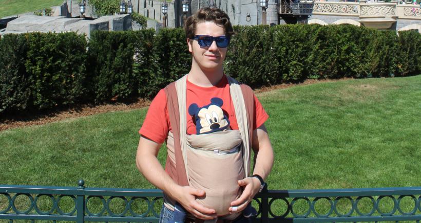 Ich mit Sonnenbrille vor einer Wiese mit Hecke. An meinem Bauch das Baby im Tragetuch, vollständig verdeckt. Es schaut nur der Kopf heraus, der mit einer Mickey-Maus-Mütze bedeckt ist.