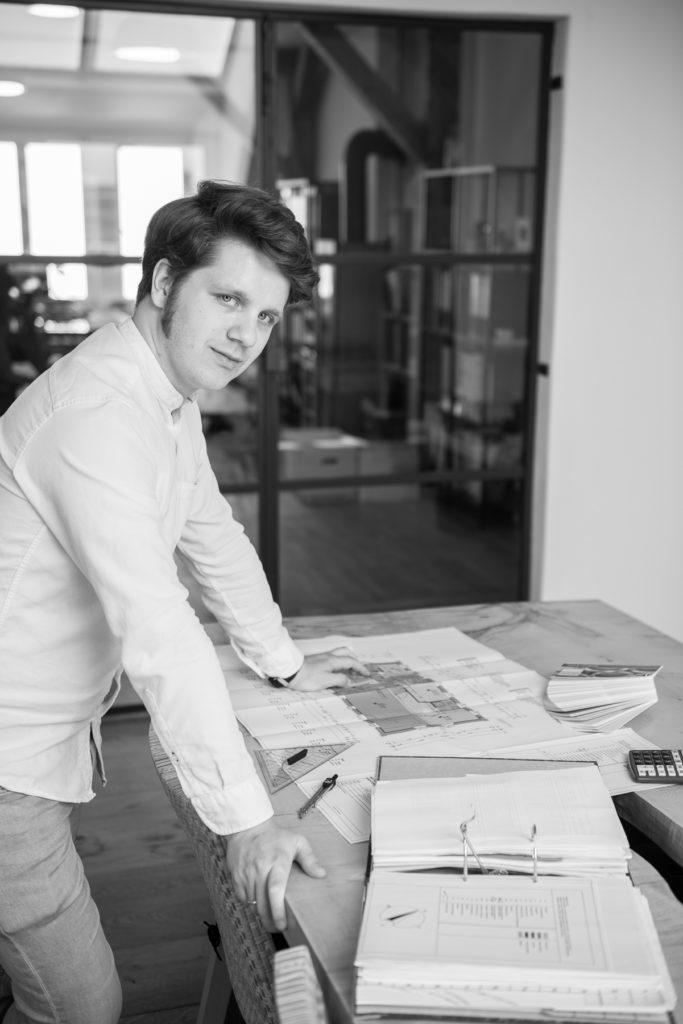 Martin an einem Holztisch stehend, darauf ein Bauplan und Arbeitsutensilien.