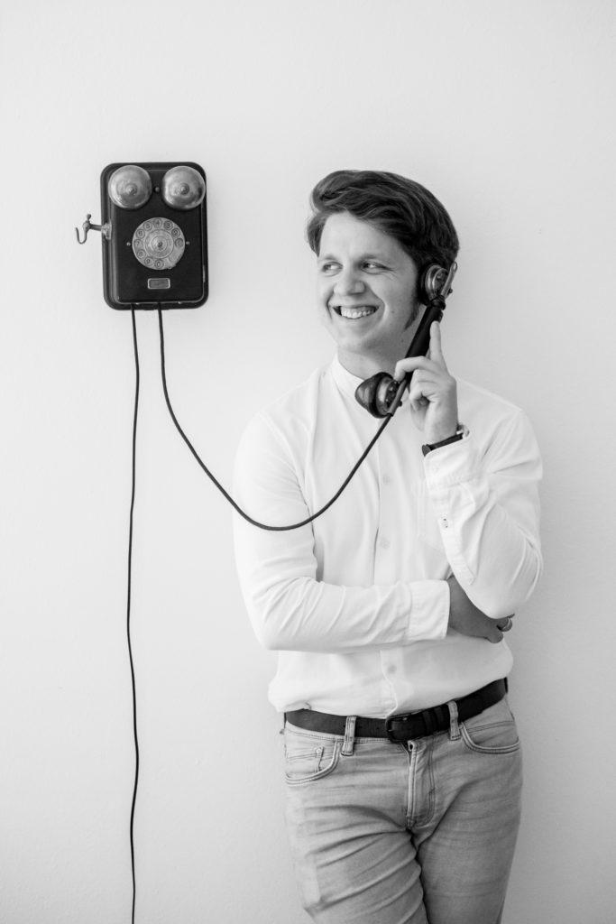 Martin an einer Wand neben einem alten Wandtelefon lehnend. Er hält den Hörer am Ohr und lacht.