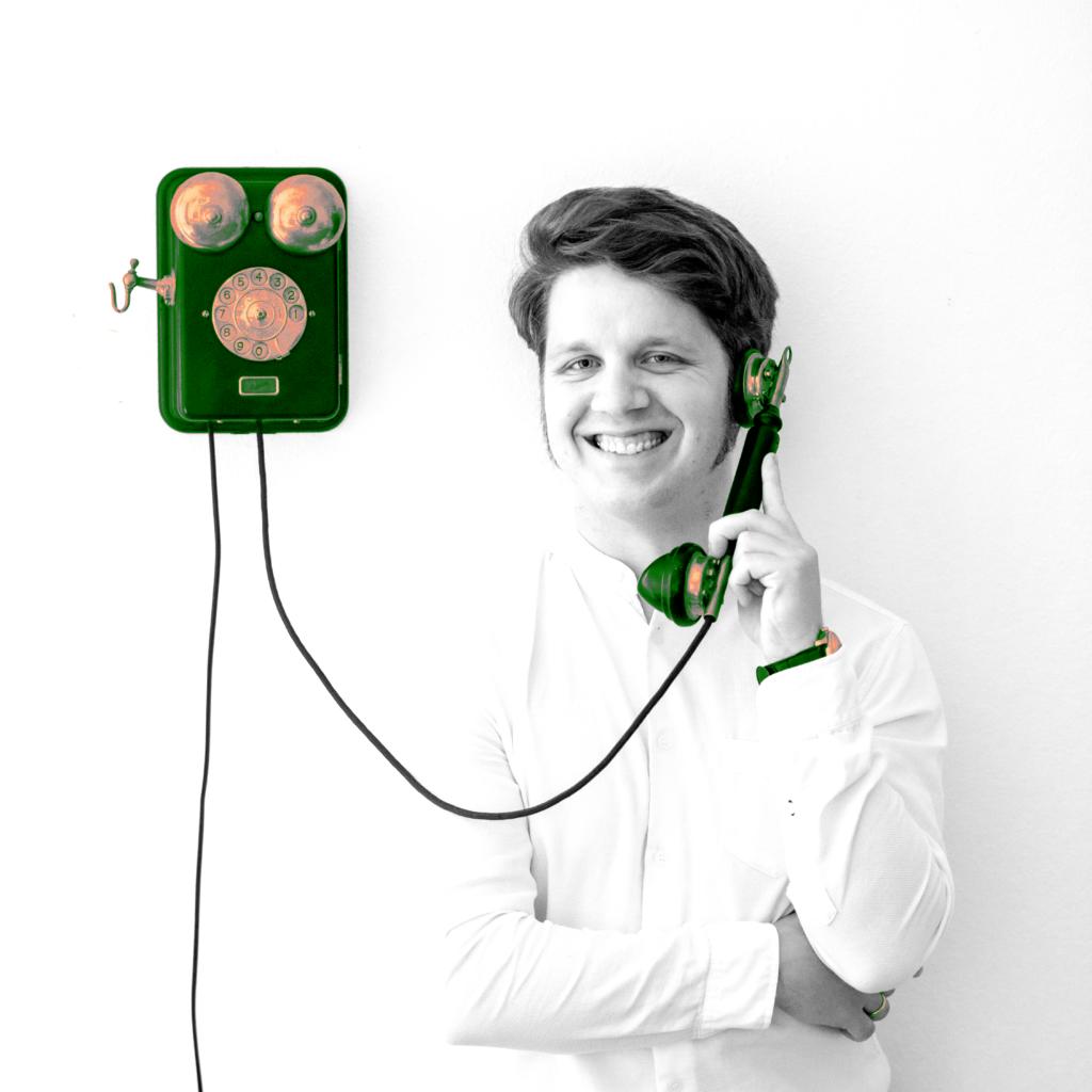 Martin an einer Wand neben einem alten Wandtelefon lehnend. Er hält den Hörer am Ohr und lächelt.